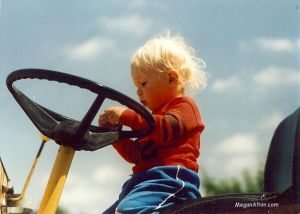 Baby Steve riding a tractor.
